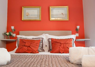 The Bedford king bed with orange cushions and matching wall