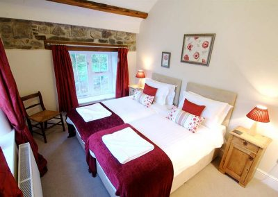 The Belstone twin bedroom with red covers and matching curtains
