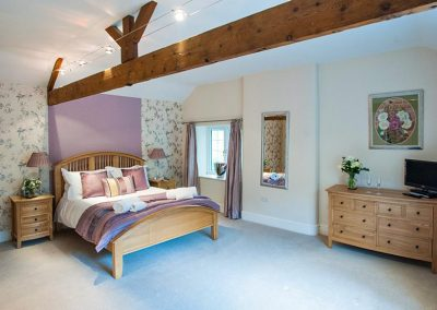 View of the Dartmoor king bedroom with exposed oak beams
