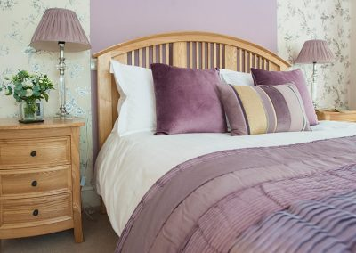 The Dartmoor king bedroom with lilac covers and lamps