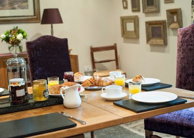 Dining room table laid with breakfast