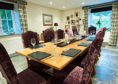 Large dining room laid for dinner with purple chairs