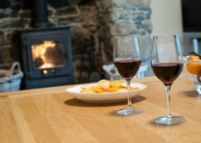 Two glasses of red wine and crisps with log burner