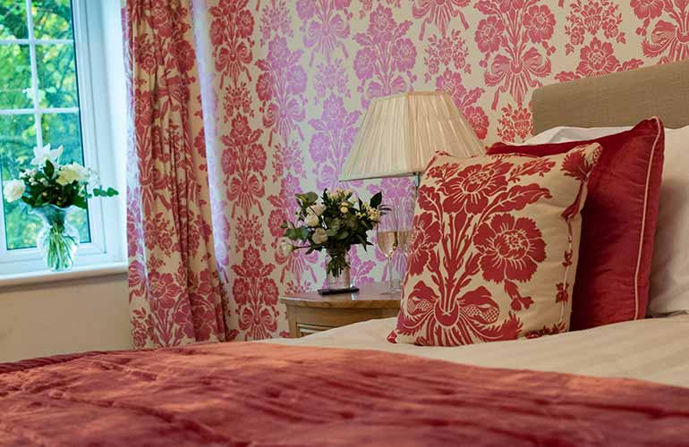 Pink flowered cushions on bed
